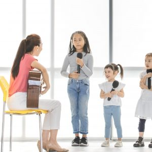 Asian teacher sitting on a chair play acoustic guitar teach Asian kids to sing a song, kids pay attention to listen to her, they stand in front of big white window.